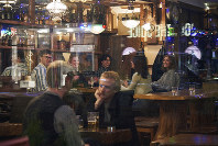 People sit in a bar in Stockholm, Wednesday, March 25, 2020. (AP Photo/David Keyton)