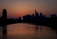 The sun sets behind the buildings of the banking district in Frankfurt, Germany, on March 28, 2020. (AP Photo/Michael Probst)