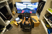 IndyCar driver Tony Kanaan, of Brazil, practices on his racing simulator in his home in Indianapolis, Saturday, March 28, 2020. (AP Photo/Michael Conroy)