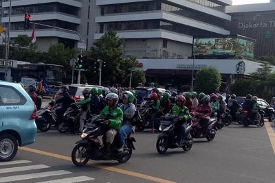 お客さんを乗せて走る「ライドシェア」のバイク=インドネシア・ジャカルタで
