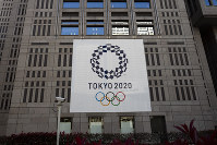 A banner promoting the Tokyo 2020 Olympics hangs on the facade of the Tokyo Metropolitan Government building, on March 25, 2020, in Tokyo. (AP Photo/Jae C. Hong)