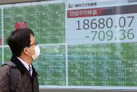 A man looks at an electronic stock board of a securities firm in Tokyo, on March 30, 2020. (AP Photo/Koji Sasahara)