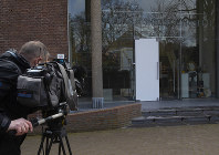 A cameraman films the glass door which was smashed during a break-in at the Singer Museum in Laren, Netherlands, on March 30, 2020. (AP Photo/Peter Dejong)