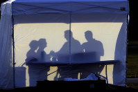 In this March 25, 2020 file photo, medical personnel are silhouetted against the back of a tent before the start of coronavirus testing in the parking lot outside of Raymond James Stadium in Tampa, Fla. (AP Photo/Chris O'Meara)
