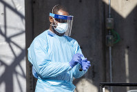 A member of the Brooklyn Hospital Center COVID-19 testing team puts on a glove before entering the testing sight, on March 26, 2020, in the Brooklyn borough of New York. (AP Photo/Mary Altaffer)