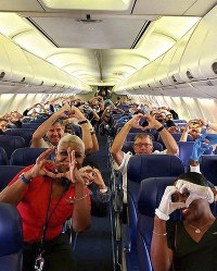 This March 27, 2020, photo provided by Southwest Airlines employee Dayartra Etheridge shows health care workers, other passengers and flight crew aboard a Southwest flight from Atlanta to New York's LaGuardia Airport holding their hands in the shape of a heart, before the plane pushed back from the gate, at Hartsfield-Jackson Atlanta International Airport. (Dayartra Etheridge via AP)