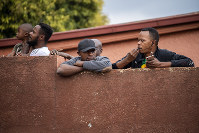 Residents of the densely populated Hillbrow district of Johannesburg, South Africa, look over the high wall of their residence, on March 29, 2020. (AP Photo/Jerome Delay)
