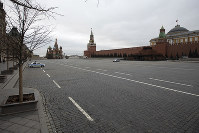 Police cars stand guard in an empty Red square, with St. Basil's Cathedral, center, and Kremlin's Spasskaya Tower, right, in Moscow, Russia, on March 30, 2020. (AP Photo/Pavel Golovkin)