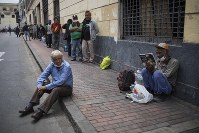 Men wait in line for a free lunch from a charity organization that serves the homeless in Lima, Peru, on March 26, 2020, on the second week of a government decreed state of emergency that restricts residents to their homes to help contain the spread of the new coronavirus. (AP Photo/Rodrigo Abd)