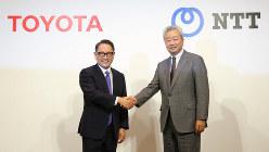 資本提携の発表会見で握手を交わすトヨタ自動車の豊田章男社長(左)とNTTの澤田純社長