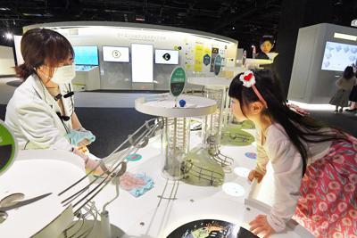 開館中、展示物に触れて遊ぶ子供たちのそばで消毒するスタッフ(左)=福岡市中央区の市科学館で2020年3月28日、森園道子撮影