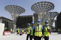 In this Oct. 8, 2019 file photo, technicians walk at the under construction site of the Expo 2020 in Dubai, United Arab Emirates. (AP Photo/Kamran Jebreili)