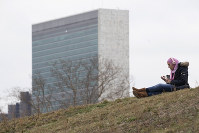 A woman listens to music at a park on Roosevelt Island, on March 17, 2020, in New York, with a United Nations building in the background. (AP Photo/Mary Altaffer)