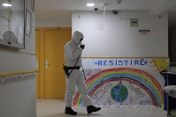A member of the UME (Emergency Army Unit) wearing a protective suit to protect against coronavirus disinfects next to a banner reading in Spanish: