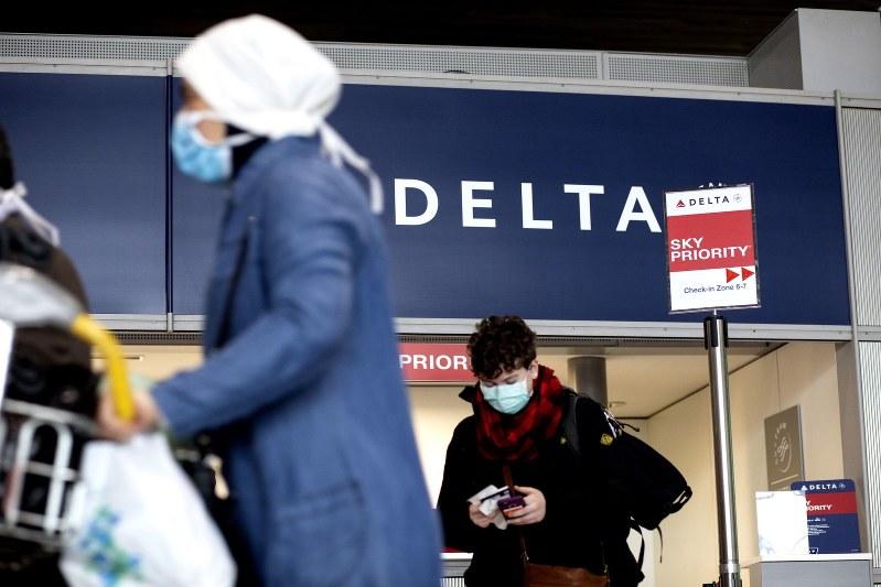 デルタ航空の空港カウンター、マスクをつける搭乗者 Bloomberg