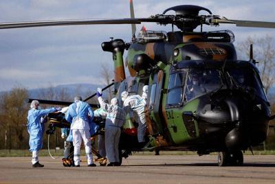 新型コロナウイルスの患者をドイツやスイスの病院に搬送するため仏軍ヘリに乗せる医療関係者=仏東部ストラスブールで30日、ロイター
