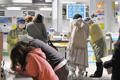 入国制限が強化される中、韓国からの便で到着した人たちに質問票の記入や2週間の待機要請について説明をする検疫官ら=成田空港で3月9日、手塚耕一郎撮影