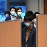 新型コロナウイルス感染拡大防止のため、山下良則社長と1対1の対面形式で行われたリコ-の入社式で、マスクをつけて順番を待つ新入社員ら=東京都大田区で2020年4月1日午前9時29分、北山夏帆撮影