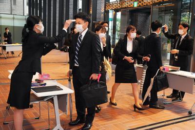 新型コロナウイルス対策で、入行式前に検温される西日本シティ銀行の新入行員たち=福岡市中央区で2020年4月1日午前8時33分、森園道子撮影