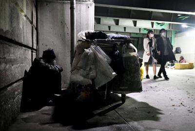 マスクをして高架下を通る人たちを眺める路上生活者の男性。拾った2枚のマスクを洗いながら使っている。「拾ったマスクをつけるのは嫌だけど、ウイルスにかかるのも嫌だ」=東京都墨田区で2020年3月22日、滝川大貴撮影