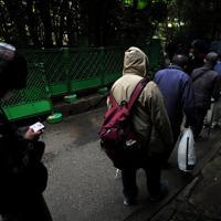 炊き出しで配られたマスクを着け、間隔を開けて並ぶ路上生活者ら=東京都豊島区で2020年3月28日、滝川大貴撮影