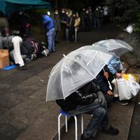 医療相談が始まるのを待つ路上生活者ら(手前)と物資の配布を受けるマスク姿の行列=東京都豊島区で2020年3月28日午後4時55分、滝川大貴撮影