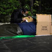 公園で段ボールに入って寒さをしのぐ路上生活者の男性にマスクを手渡すボランティアの男性=東京都豊島区で2020年3月25日午後10時10分、滝川大貴撮影