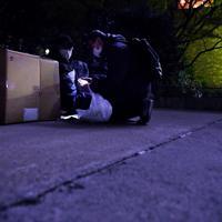 公園で段ボールに入って寒さをしのぐ路上生活者の男性にマスクを手渡すボランティアの男性=東京都豊島区で2020年3月25日午後10時16分、滝川大貴撮影