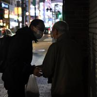 路上生活者の男性にマスクを手渡すボランティアの男性=東京都豊島区で2020年3月25日午後9時48分、滝川大貴撮影