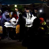 マスク姿で間隔を空けて並ぶ路上生活者ら(手前)に弁当を配るボランティアたち=東京都豊島区で2020年3月28日午後6時9分、滝川大貴撮影