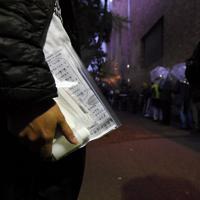 マスクやカイロ、新型コロナウイルス感染予防の方法が書かれた用紙をもらい、食事の支給まで間隔を空けて並ぶ路上生活者ら=東京都豊島区で2020年3月28日午後5時50分、滝川大貴撮影