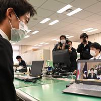 新型コロナウイルス感染拡大防止のため、パソコンの動画で小池百合子都知事のメッセージを聞く新入職員(左)=東京都庁で2020年4月1日午前11時4分、大西岳彦撮影