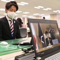 新型コロナウイルス感染拡大防止のため、パソコンの動画を通じて新入職員(左)にメッセージを伝える小池百合子都知事=東京都庁で2020年4月1日午前11時2分、大西岳彦撮影