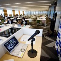 新型コロナウイルス感染拡大を受け、「GMOインターネットグループ」は入社式を在宅勤務(テレワーク)で開催し、新入社員165名がオンライン上で参加した。入社式を行う予定だった会場では、人事部など限られた社員人数が出社し、PCで入社式を取り仕切っていた=東京都渋谷区で2020年4月1日午後0時28分、吉田航太撮影