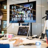 新型コロナウイルス感染拡大を受け、在宅勤務(テレワーク)で入社式に参加するGMOインターネットグループの新入社員たち(中央奥画面内)=東京都渋谷区で2020年4月1日午後0時8分、吉田航太撮影
