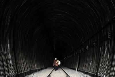 震災の影響で使われていない鉄道のトンネルを歩く女性。市役所から自宅へ戻る途中といい、「峠を越えなくていいから、こっちのほうが早いんです」と話した=宮城県気仙沼市で2011年4月20日午後0時24分、久保玲撮影