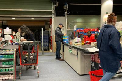 スーパーは客の入店人数を制限し、店員らもマスクに手袋で感染予防対策している=筆者撮影