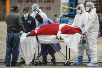 A body wrapped in plastic that was unloaded from a refrigerated truck is handled by medical workers wearing personal protective equipment due to COVID-19 concerns, on March 31, 2020, at Brooklyn Hospital Center in Brooklyn borough of New York. (AP Photo/John Minchillo)