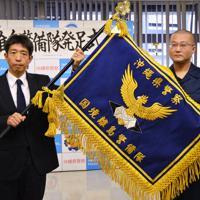 沖縄県警に国境離島警備隊が1日新設され、隊旗を授与された小林雅哉隊長(右)=那覇市の県警本部で1日、竹内望撮影