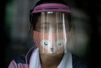 A volunteer wearing a face shield and mask manages a counter of COVID-19 infection screening center at the Chulalongkorn University health service center in Bangkok, Thailand, on April 1, 2020. (AP Photo/Gemunu Amarasinghe)