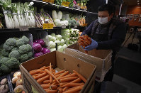 A worker, wearing a protective mask and gloves against the COVID-19 coronavirus, stocks produce before the opening of Gus's Community Market, on March 27, 2020, in San Francisco. (AP Photo/Ben Margot)