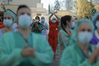 Health workers applaud as people react from their houses in support of the medical staff that are working on the COVID-19 virus outbreak at the Gregorio Maranon hospital in Madrid, Spain, on April 1, 2020. (AP Photo/Manu Fernandez)