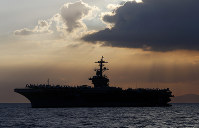 In this April 13, 2018 file photo, the USS Theodore Roosevelt aircraft carrier is anchored off Manila Bay west of Manila, Philippines. (AP Photo/Bullit Marquez)