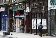 A man walks by boarded up bars as the UK continues its lockdown to help curb the spread of the coronavirus, in Glasgow, Scotland, on April 1, 2020. (Andrew Milligan/PA via AP)