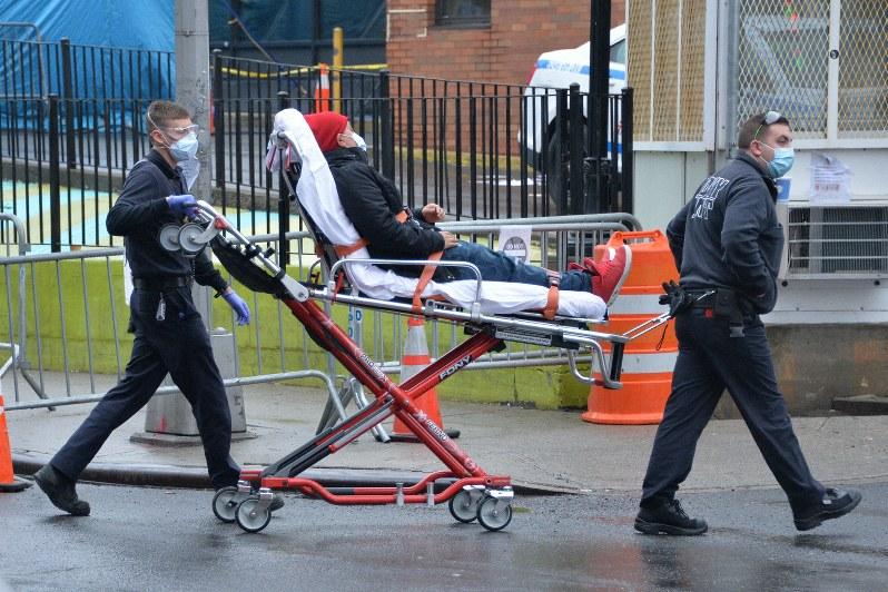 新型コロナウイルス患者が多発している米ニューヨーク市で、クイーンズ地区のエルムハースト病院に運び込まれる患者=3月29日