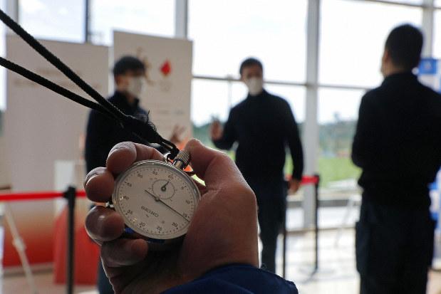 Jヴィレッジで展示が始まった東京オリンピックの聖火の前で写真を撮る人たちは、新型コロナウイルスの世界的流行をうけ、滞留しすぎないよう、近くで見物する時間が30秒ほどに限られた=福島県楢葉町で2020年4月2日、和田大典撮影