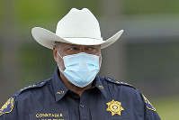 Harris County Constable Sherman Eagleton wears a face mask while working at a newly opened free drive through Covid-19 testing site operated by United Memorial Medical Center, on April 2, 2020, in Houston. (AP Photo/David J. Phillip)