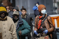 A pedestrian wearing personal protective equipment due to COVID-1 coronavirus and concerns stands in line for a free food handout at the Bowery Mission, on April 1, 2020, in New York. (AP Photo/John Minchillo)