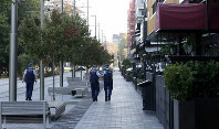 Police patrol the empty streets of the central business district in Christchurch, New Zealand, on March 26, 2020. (AP Photo/Mark Baker)