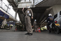 Policemen wearing face masks to protect themselves from the new coronavirus at a health checkpoint in Bangkok, Thailand, on April 3, 2020. (AP Photo/Sakchai Lalit)